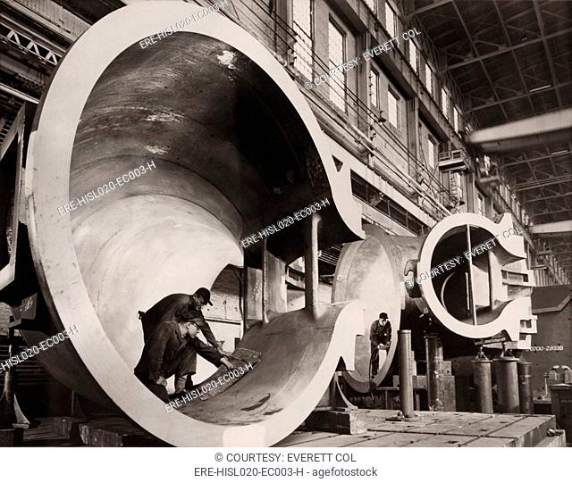 Men in the casing sections of giant turbines during construction at the Hungry Horse Dam in Montana. The dam was authorized for construction in 1944