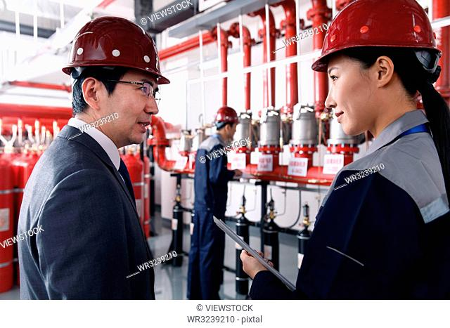 Technical personnel in the factory fire control room inspection