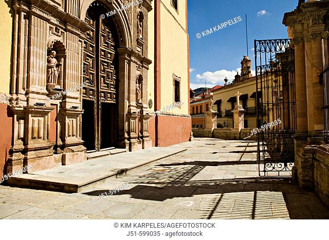 Entrance and ornate carved doorway of exterior of Basilica de Nuestra Señora, metal gate open, stone courtyard. Guanajuato. Mexico