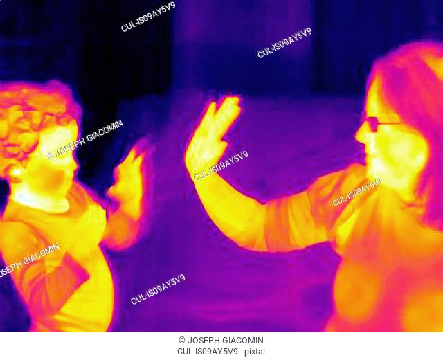 Thermal image of mature woman and son playing hand clapping game