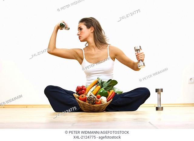 Young woman with vegetable bowl, a cucumber in one hand and a barbell in the other (model-released)