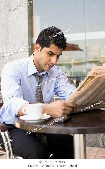 Businessman reading a newspaper at a sidewalk cafe, Gurgaon, Haryana, India