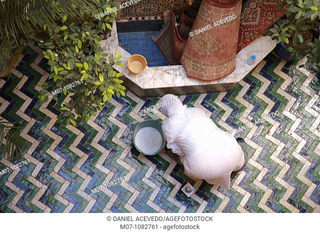 Woman cleaning a Riad flor