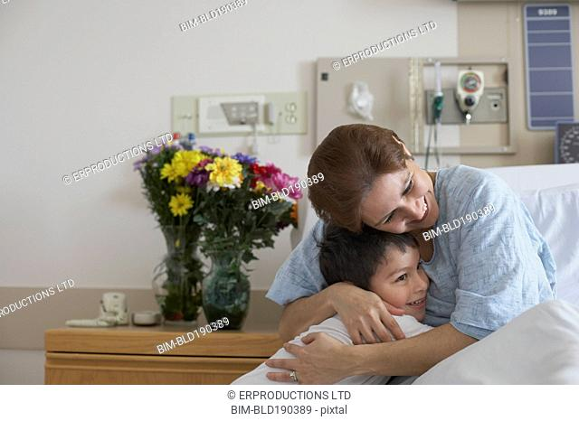 Hispanic mother in hospital bed hugging son