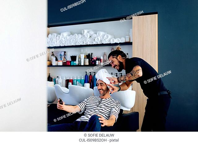 Male hairstylist and male customer taking smartphone selfie in hair salon