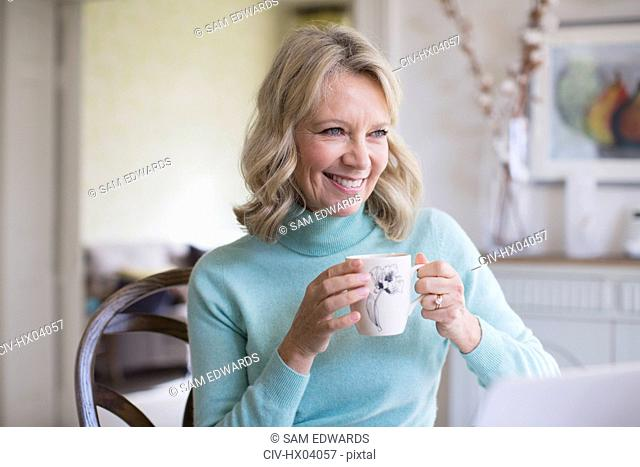 Smiling mature woman drinking coffee