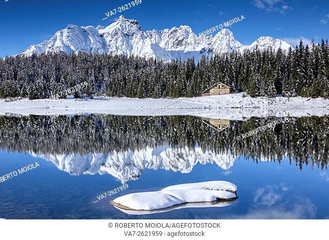 Wooden chalet surrounded by snowy peaks and woods reflected in Lake Palù Malenco Valley Valtellina Lombardy Italy Europe