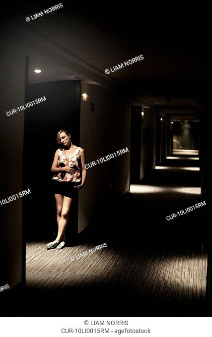 a girl in a hotel corridor, waiting in top lit moody light