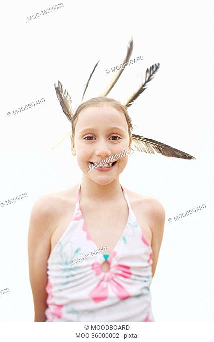 Portrait of happy girl with feathers in hair over white background