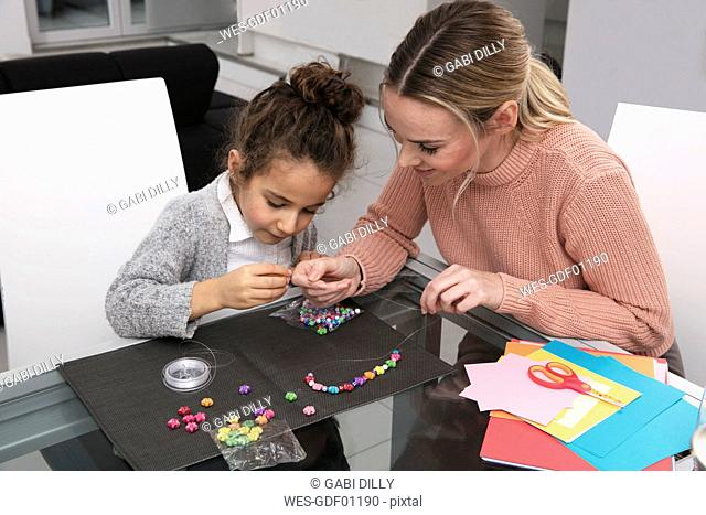 Mother and little daughter stringing beads for creating a necklace