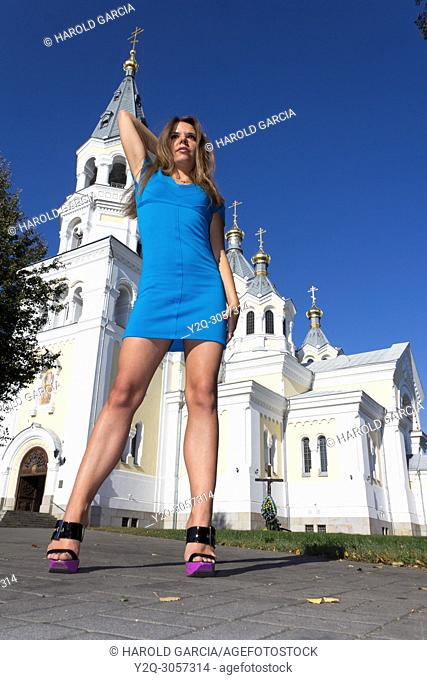Beautiful, attractive Ukrainian woman wearing a blue dress posing near the Orthodox Cathedral of Transfiguration for a photographic sequence in Zhitomyr