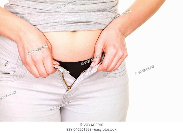 Woman with belly fat getting dressed putting pants on. Overweight female trying to fasten too small trousers isolated. Weight gain diet concept