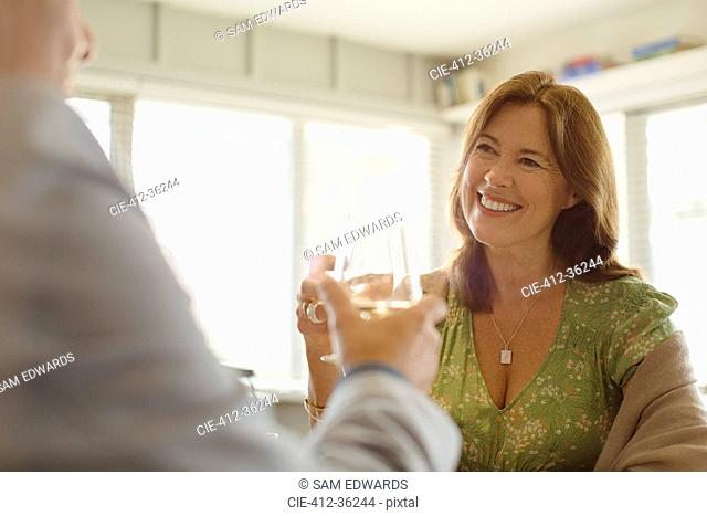 Smiling couple toasting wine glasses at restaurant