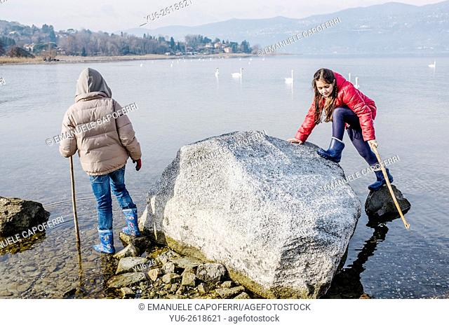 Children playing on large rock from the water of Lake Maggiore, Italy