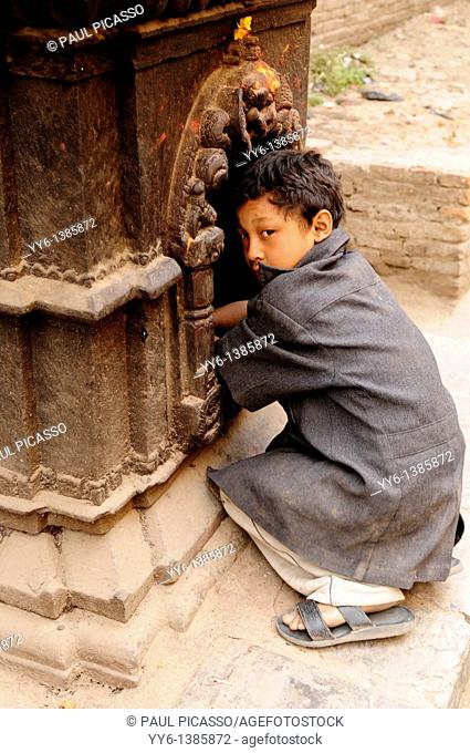 young nepalis boy praying at street shrine, the nepalis , life in kathmandu , kathmandu street life , nepal