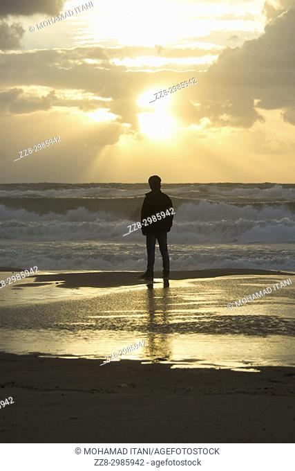 Rear view of a young silhouetted man standing on the beach at sunset