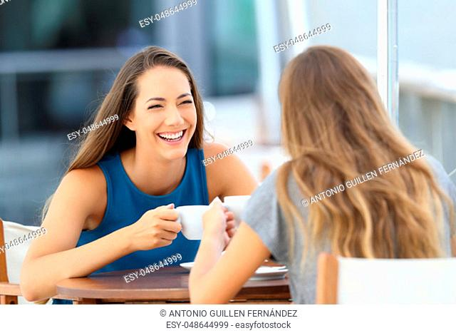 Two happy friends talking and laughing sitting in a restaurant terrace