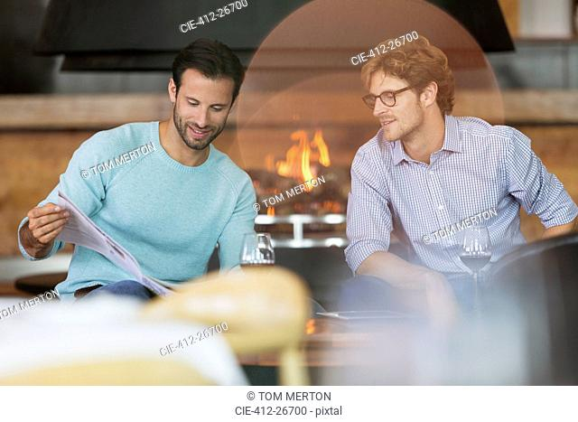 Men drinking red wine and reading brochure