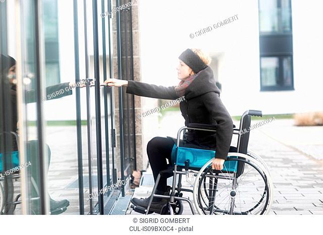 Woman in wheelchair opening door to building
