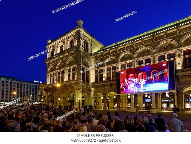 Staatsoper, people look at the transfer of the current performance of the opera on a large screen in front of the Opera, Wien, Vienna, 01