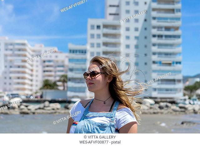 Young woman at the beach, wearing sunglasses, portrait