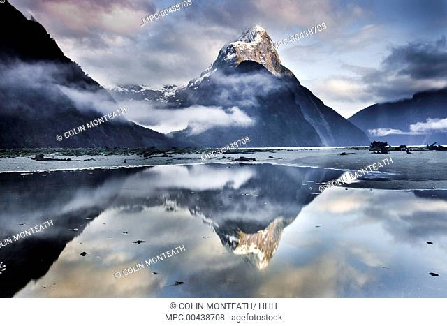 Mitre Peak reflecting in Milford Sound in winter at dawn, Fiordland National Park, New Zealand