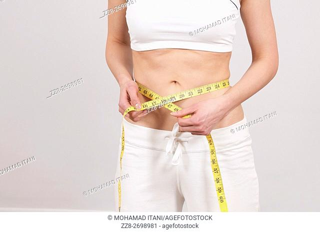 Woman measuring waist with tape measure