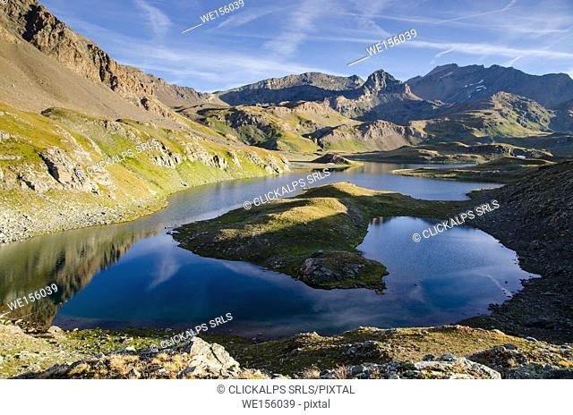 The calm surface of an alpine lake, under rocky ridges, in the early morning in summertime. (Valsavarenche, Aosta Valley, Italy)