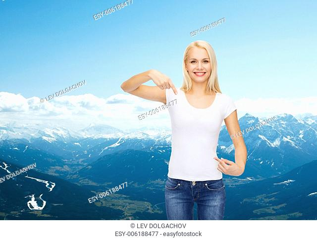 t-shirt design concept - smiling young woman pointing finger to blank white t-shirt