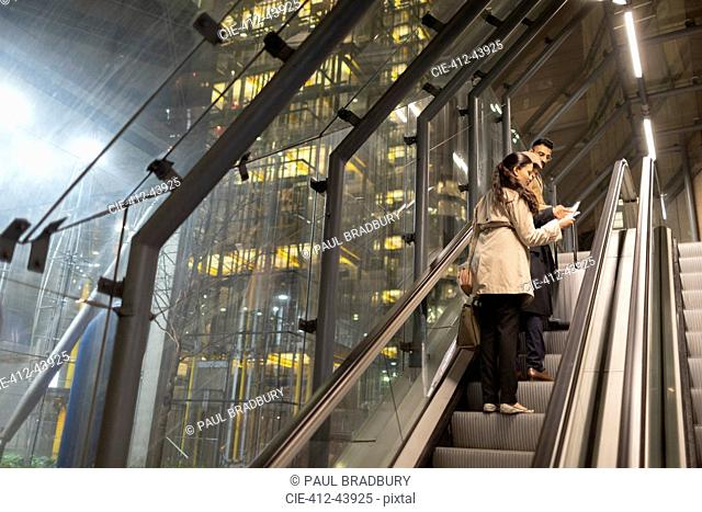 Business people with suitcase talking on urban escalator at night