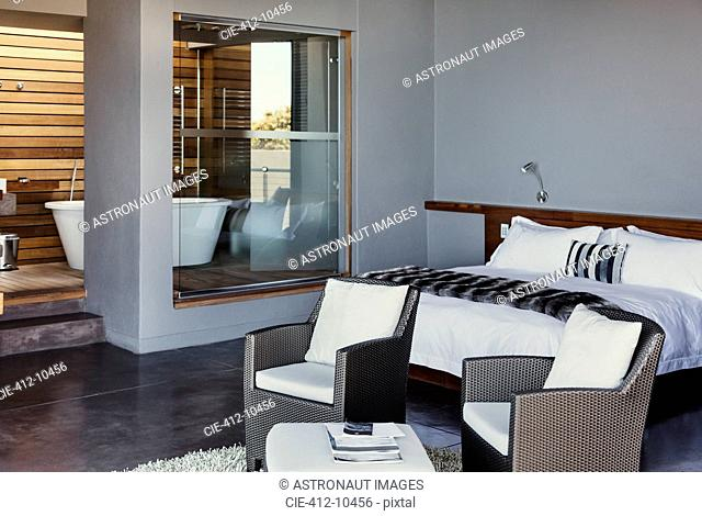 Bed and armchairs in modern bedroom