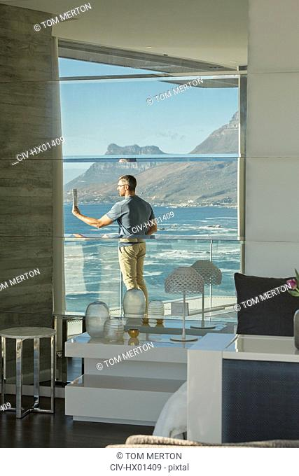 Reflection of man using digital tablet camera on luxury balcony with ocean view
