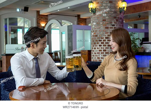 Young smiling businessman and businesswoman toasting