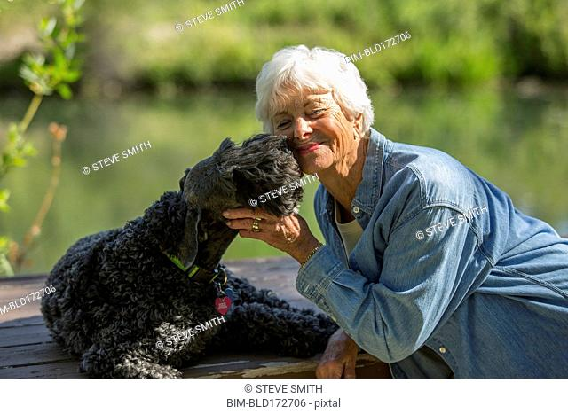 Older Caucasian woman hugging dog in park