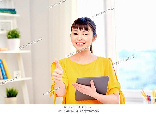 people, education, high school and learning concept - happy asian young woman student with tablet pc computer, book and notepads writing at home