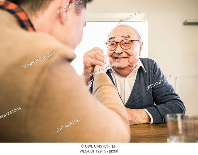 Smiling senior man arm wrestling with young man