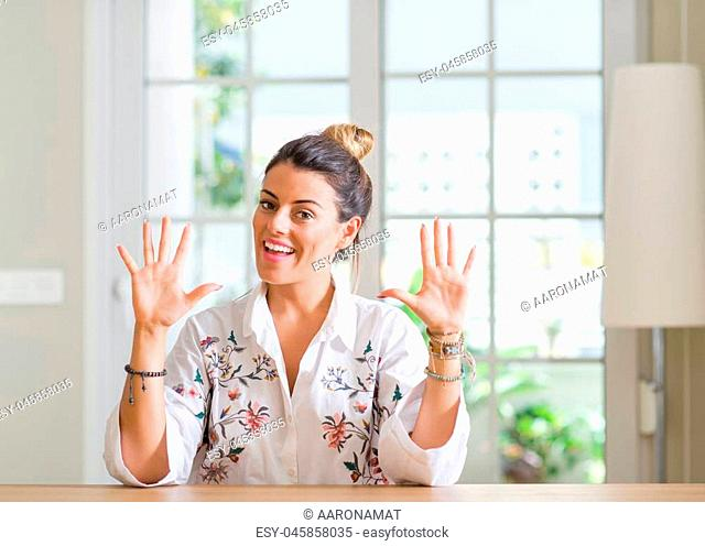 Young woman at home showing and pointing up with fingers number ten while smiling confident and happy