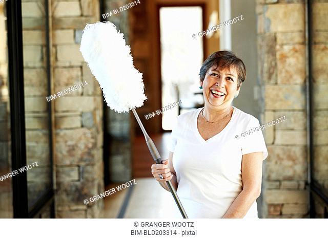 Smiling Hispanic woman holding duster