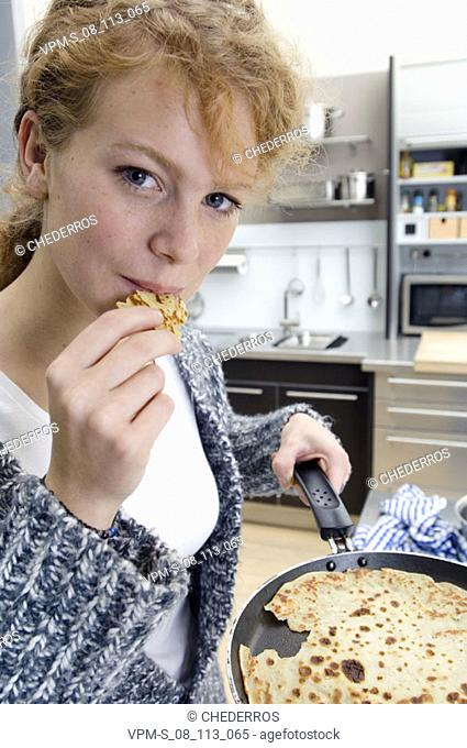 Portrait of a young woman eating an omelet in the kitchen