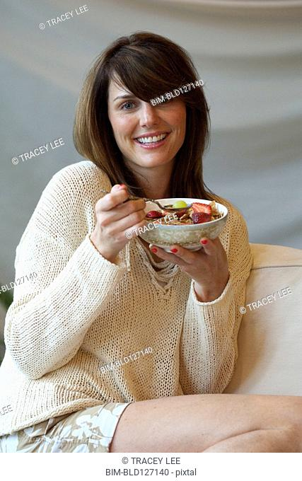 Caucasian woman eating bowl of fruit