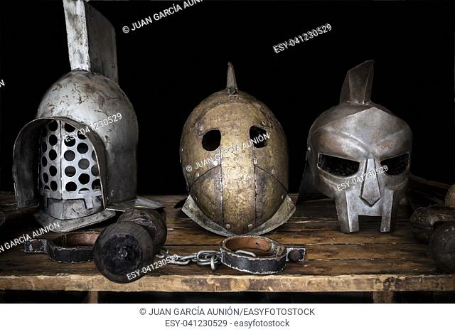 Gladiators table with helmets, swords and shakles. Ancient roman reconstruction