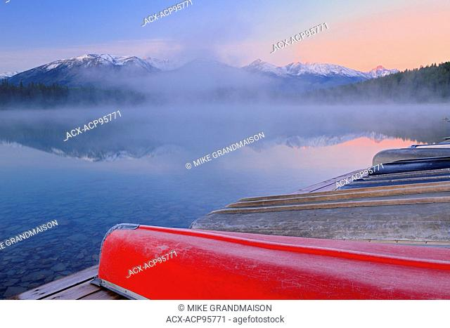 Canoes and Pyramid Lake in fog at dawn Jasper National Park Alberta Canada