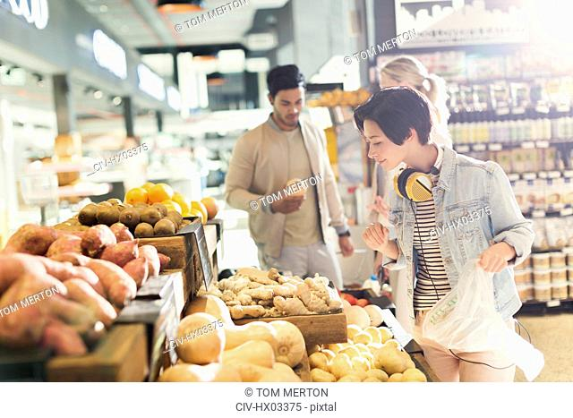 Young woman with headphones grocery shopping, browsing produce in market