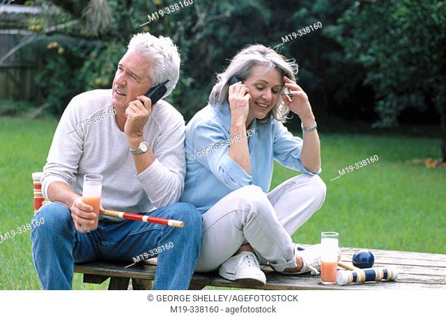 Mature couple using cell phones