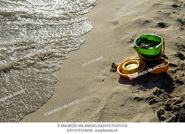 Beach toys left on the shore near the undertow