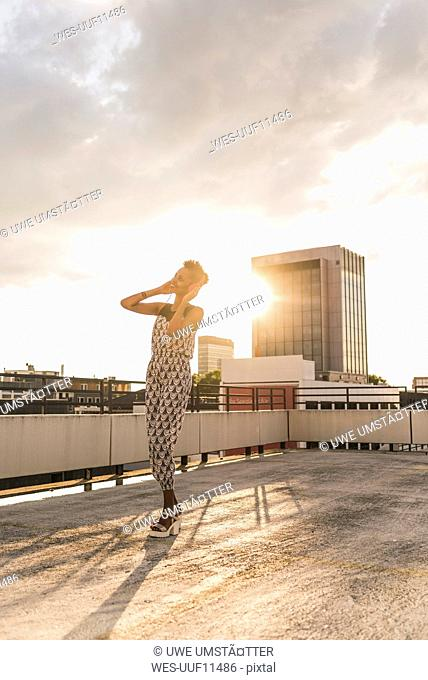 Happy young woman with headphones on rooftop