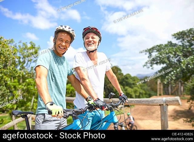 Portrait confident father and son mountain biking on sunny trail