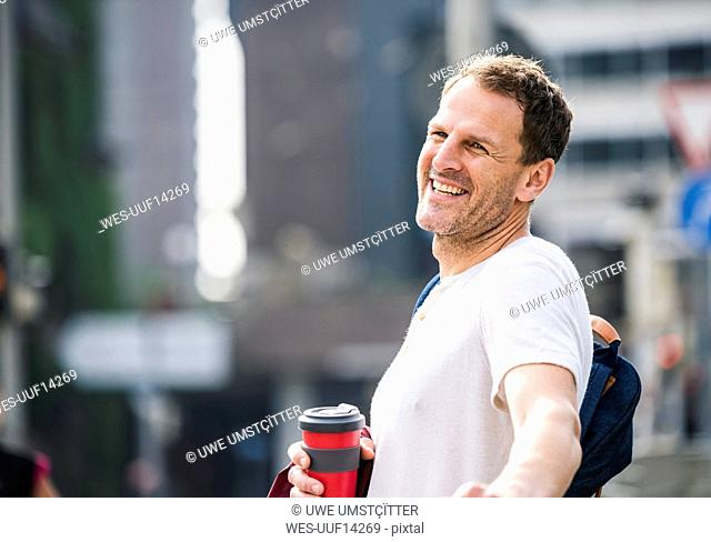 Portrait of happy man with takeaway coffee in the city