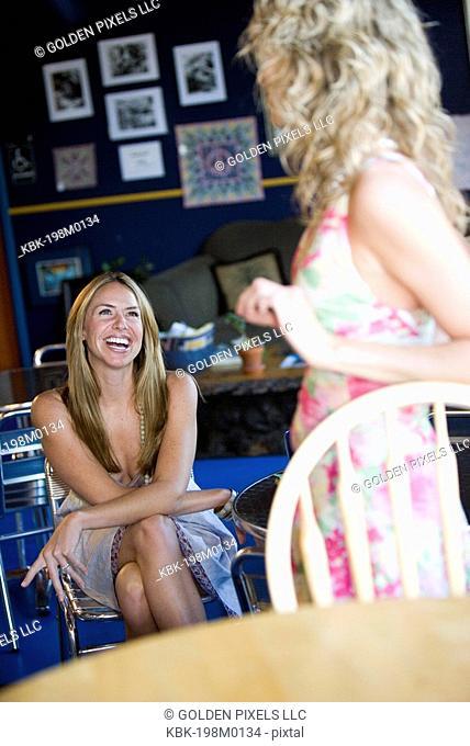 Two young women conversing in cafi