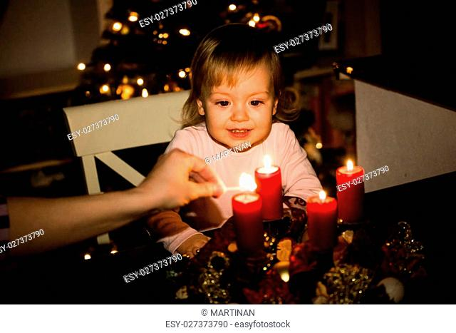 Child watching lighting of advent wreath with red candles, christmas tree in background